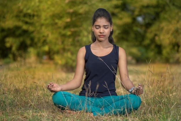 Femme faire du yoga en plein air. femme exerçant vital et méditation pour le mode de vie fitness à la nature. yoga conceptuel. détendez-vous dans la nature.