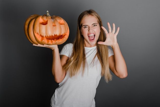 Femme, faire, effrayant, faces, à, halloween, jack o lantern, citrouille, isolé, sur, gris