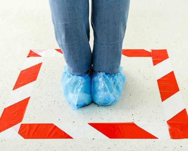 Femme faire la queue en gardant la distance sociale portant des couvre-chaussures, des couvre-chaussures médicaux en magasin, supermarché, hôpital.