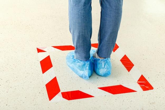 Femme faire la queue en gardant la distance sociale portant des couvre-chaussures