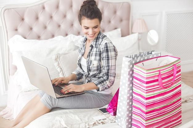 Femme faisant des achats en ligne. femme à l'intérieur avec des sacs à provisions et un ordinateur portable.