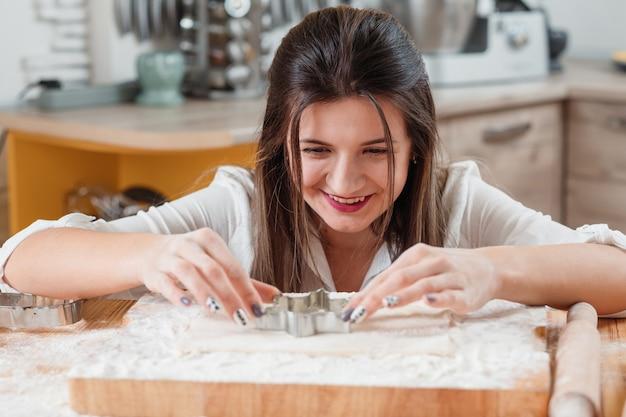 Femme faisant à l'aide d'un emporte-pièce pour faire un cookie
