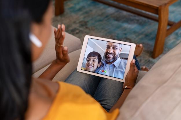 Femme faisant un appel vidéo avec sa famille