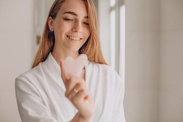 Femme faisant l'auto-massage avec la pierre de gua sha de quartz rose