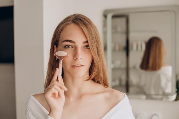 Femme faisant un auto-massage avec un rouleau facial en quartz rose