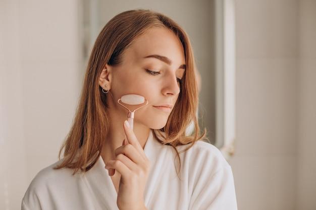 Femme Faisant Un Auto-massage Avec Un Rouleau Facial En Quartz Rose Photo gratuit