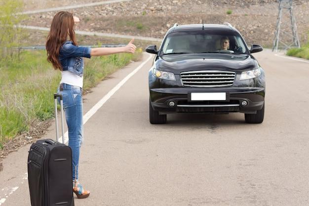 Femme faisant de l'auto-stop après une panne avec sa voiture