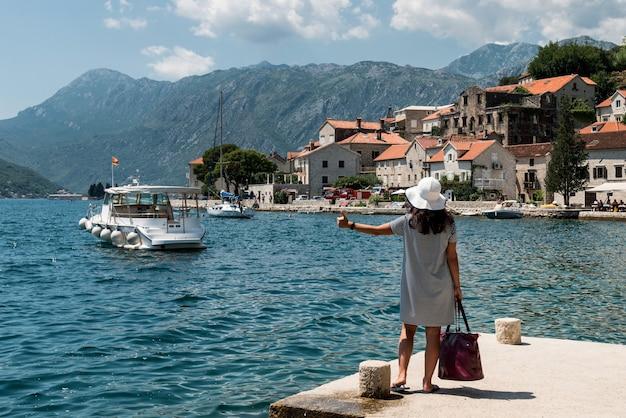Femme faisant de l'auto-stop sur une jetée. une fille attend un bateau sur la jetée.