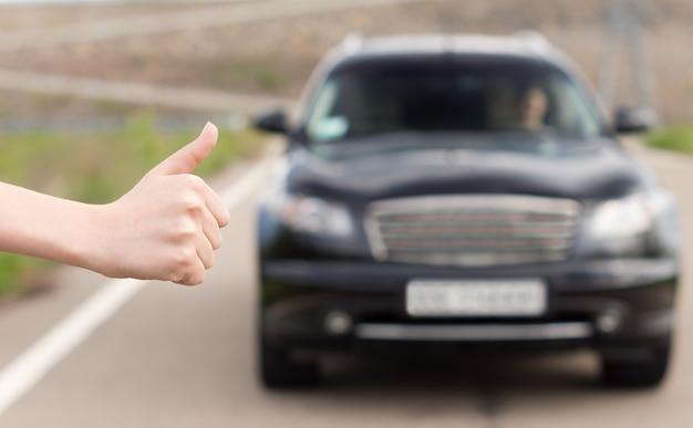 Femme faisant de l'auto-stop sollicitant un tour