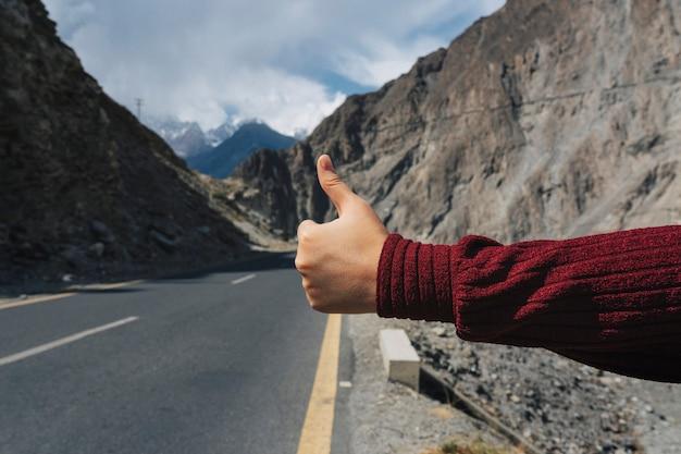 Femme faisant de l'auto-stop à travers le pays
