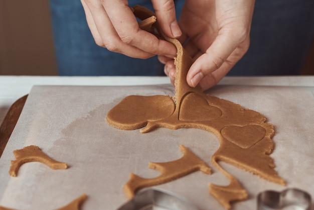 Femme faisant des biscuits de pain d'épice en forme de coeur