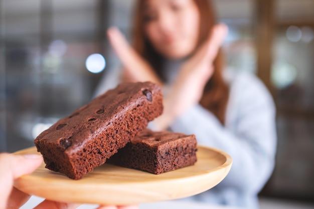 Une femme faisant des bras croisés signe pour refuser un gâteau brownie dans une assiette en bois de quelqu'un