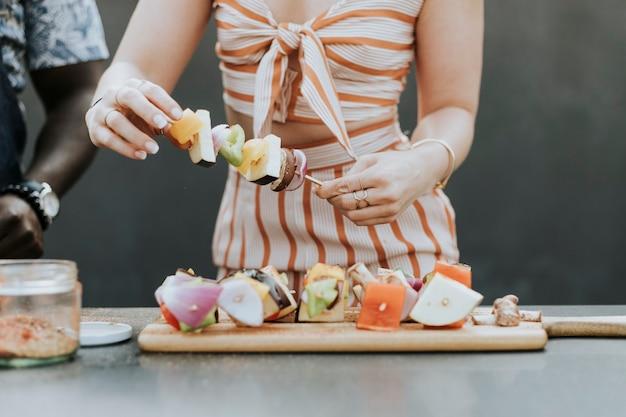 Femme faisant des brochettes de barbecue pour une fête