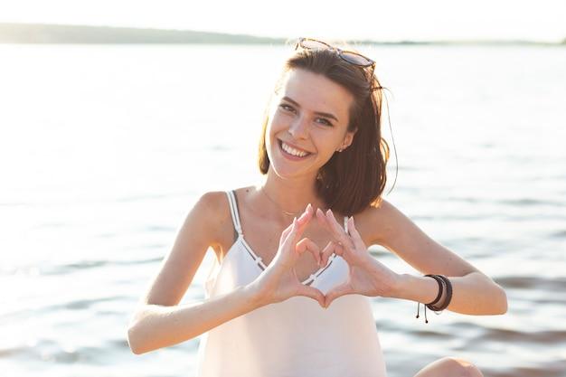 Femme faisant un coeur avec ses mains