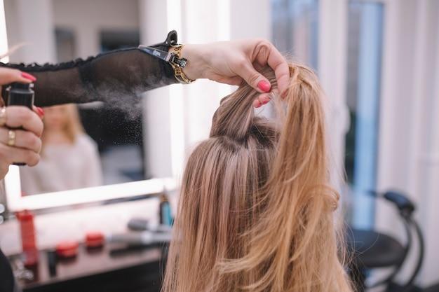 Femme faisant la coiffure pour le client