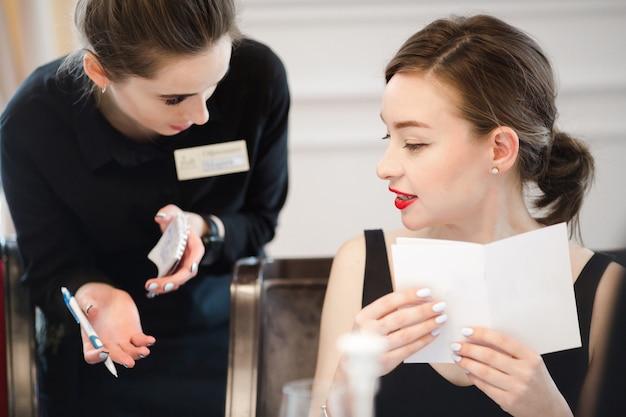 Femme faisant une commande à partir du menu de la serveuse