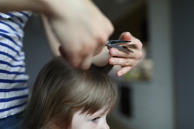 Femme faisant la coupe de cheveux à l'enfant dans un appartement