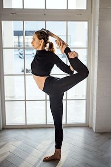 Femme faisant du ballet, de la danse et de la gymnastique dans le salon près de la fenêtre. danseuse mignonne en costume noir debout sur la pointe de ses orteils.