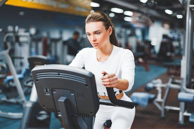 Femme faisant du cyclisme en salle faisant de l'entraînement cardio sur vélo de gym à l'intérieur.