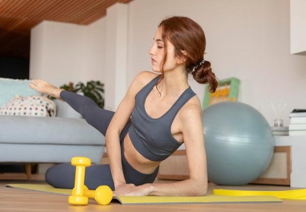 Femme faisant du fitness à la maison sur le tapis