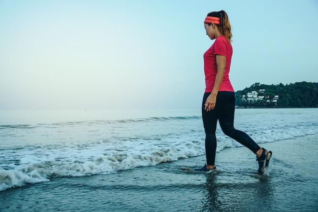 Femme faisant du jogging sur la plage le matin