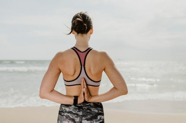 Femme faisant du namaste derrière son dos