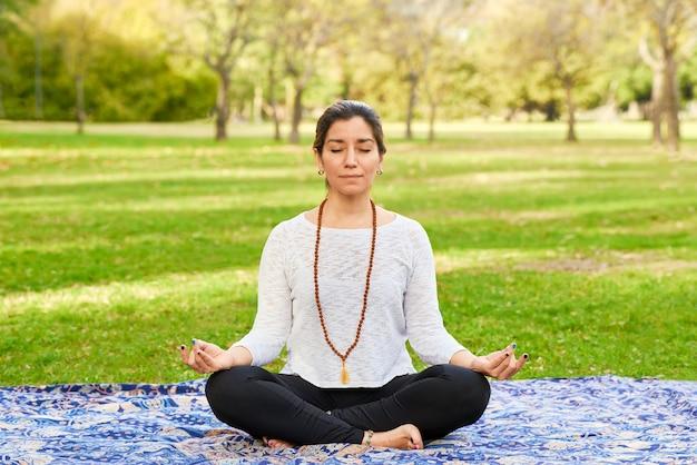Femme faisant du reiki et du yoga pose dans une pose de chakra de parc