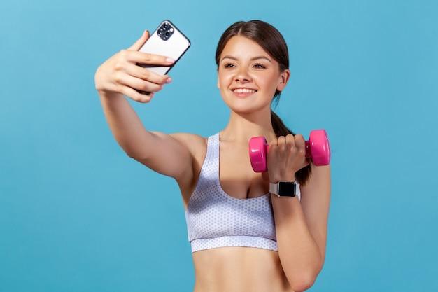 Femme faisant du selfie faisant de l'exercice avec des haltères, via une application sur un smartphone, un blog