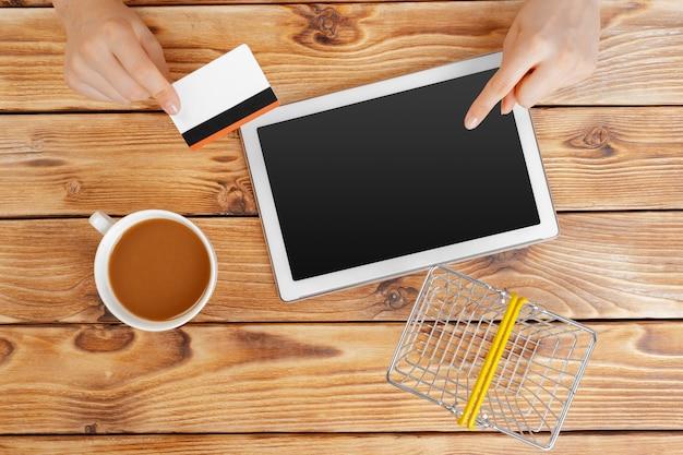 Femme faisant du shopping à l'aide d'un tablet pc et d'une carte de crédit