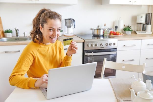 Femme faisant du shopping en ligne et payant avec carte de crédit or