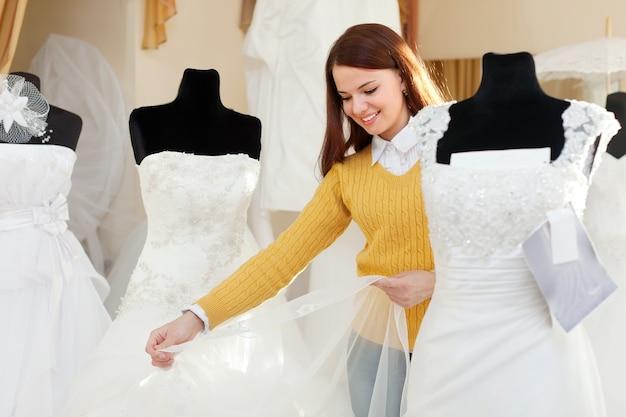 Femme faisant du shopping pour la tenue de mariage en boutique de mariée
