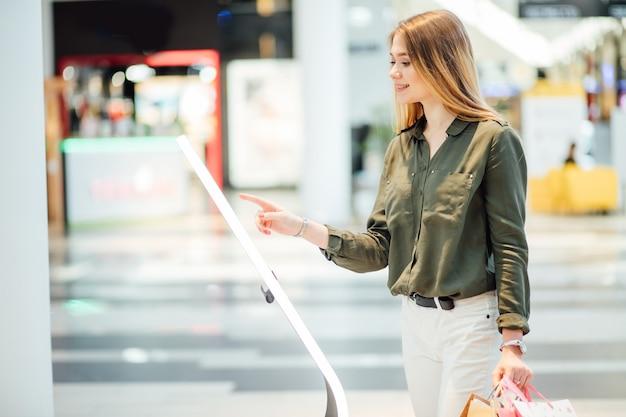 Femme faisant du shopping. à la recherche sur le panneau d'information avec la carte du centre commercial