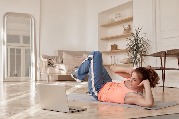 Femme faisant du sport devant un ordinateur portable à la maison