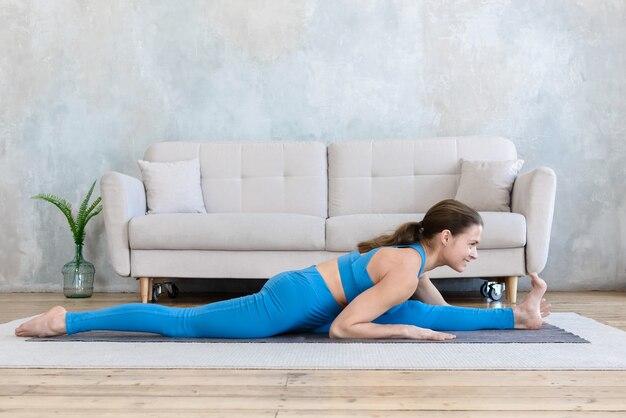 Femme faisant du sport à la maison faisant du yoga qui s'étend tout en étant assis sur la ficelle sur le tapis