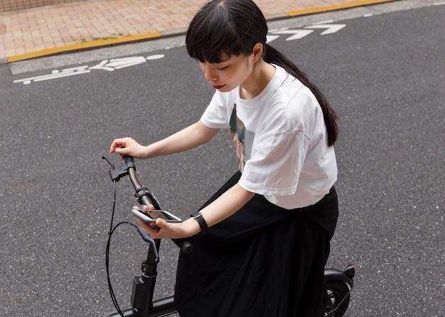 Femme faisant du vélo électrique dans la ville et tenant un smartphone