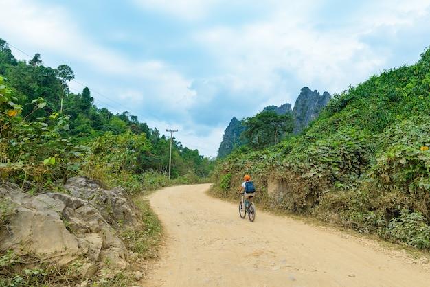 Femme faisant du vélo de montagne sur un chemin de terre dans un paysage pittoresque autour de vang vieng, destination de voyage pour routards au laos