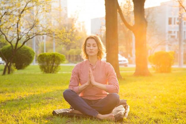 Femme faisant du yoga assis sur l'herbe verte contre le du parc de la ville.