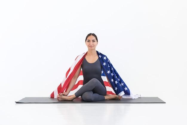 Femme faisant du yoga assis sur le tapis avec le drapeau américain. concept de la fête de l'indépendance de l'amérique du 4 juillet. fond blanc