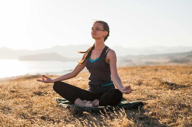 Femme faisant du yoga au lever du soleil