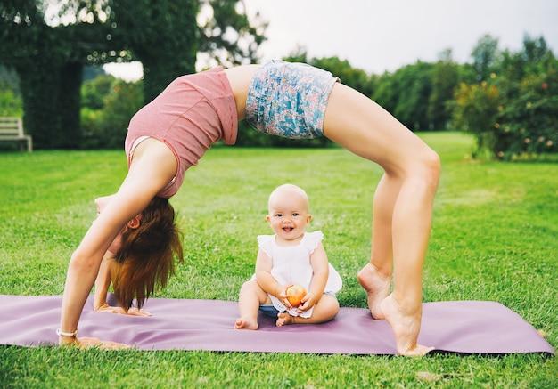 Femme faisant du yoga avec bébé dans un parc d'été famille à l'extérieur parent avec enfant passe du temps ensemble