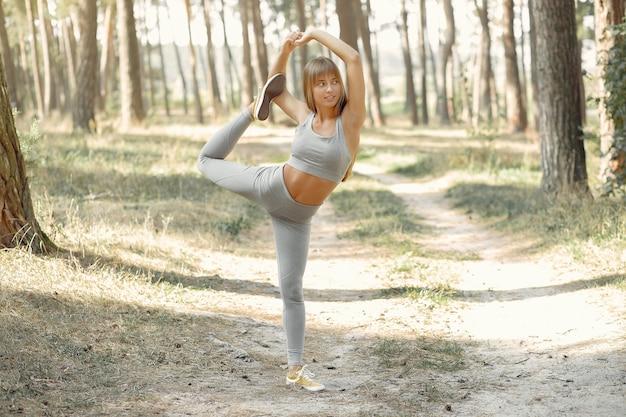 Femme faisant du yoga dans une forêt d'été