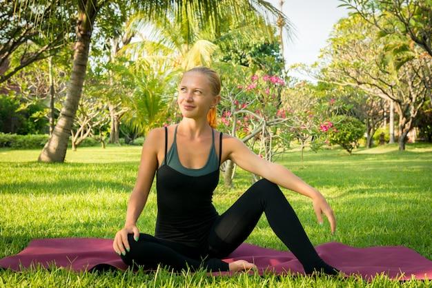 Femme faisant du yoga dans le jardin