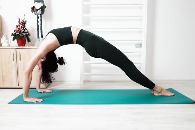 Femme faisant du yoga dans sa maison