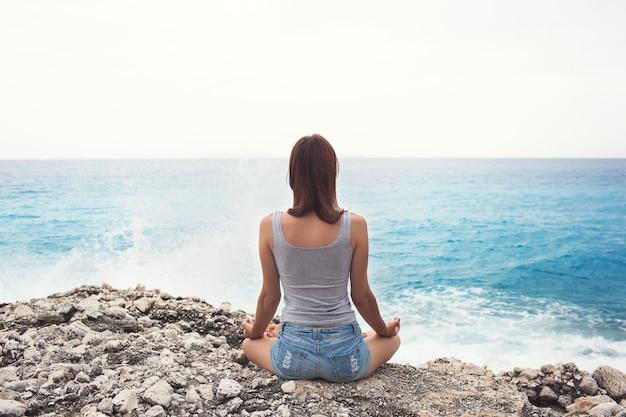 Femme faisant du yoga sur le fond de la mer