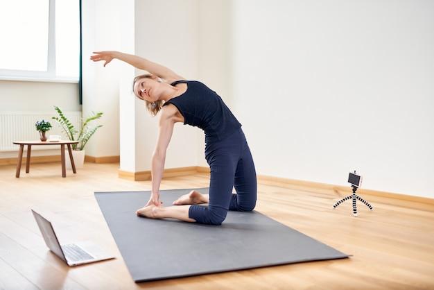 Femme faisant du yoga en ligne. ordinateur et caméra dans son salon. mode de vie sain et concepts de travail à distance