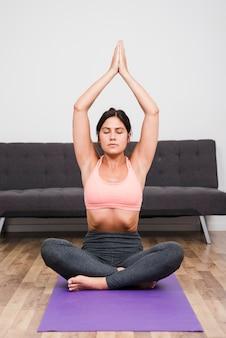 Femme faisant du yoga à la maison