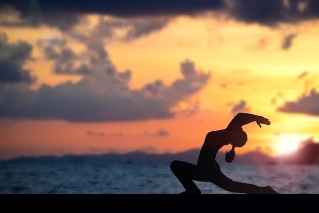 Femme faisant du yoga sur la plage