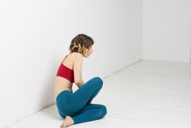 Femme faisant du yoga pleine longueur à l'intérieur des leggings bleus débardeur rouge.