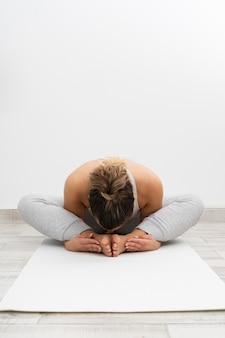 Femme faisant du yoga sur un tapis blanc