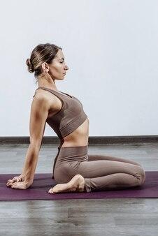 Femme faisant du yoga sur tapis à la maison